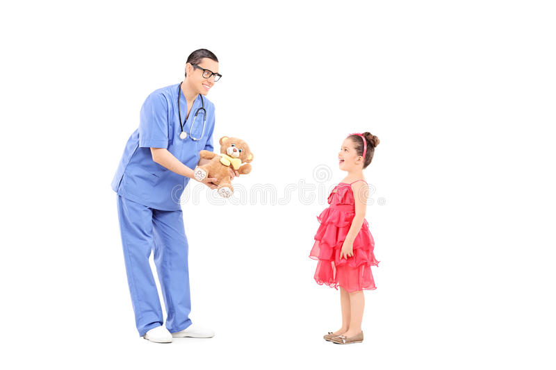 Doctor giving teddy bear to a surprised little girl stock photos