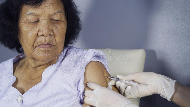 Doctor giving vaccine injection into senior woman royalty free stock images
