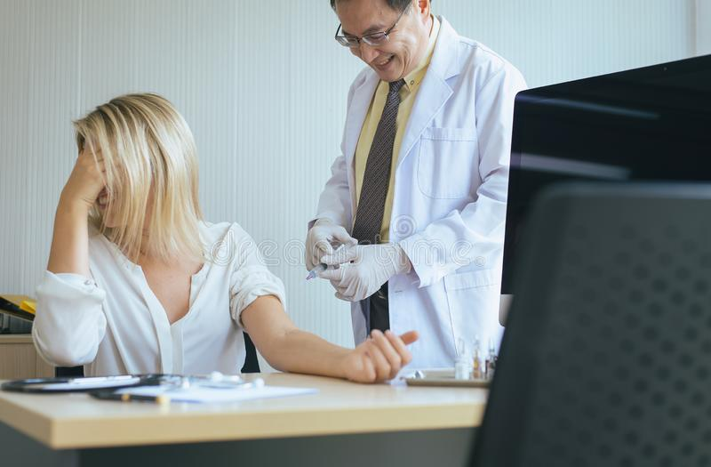 Doctor giving vaccine to woman patient with injection or syringe in hospital room royalty free stock image