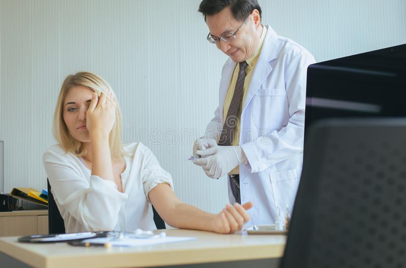 Doctor giving vaccine to frightened patient woman with injection or syringe in hospital stock images
