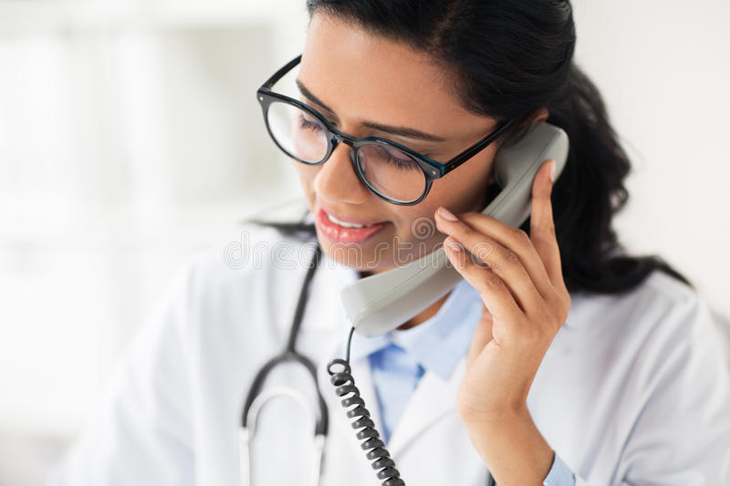 Doctor in glasses calling on phone at hospital. Medicine, people and healthcare concept - happy female doctor in glasses calling on phone at hospital stock photo
