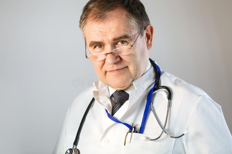 The doctor with glasses and a stethoscope looks into his eyes. Close-up royalty free stock images
