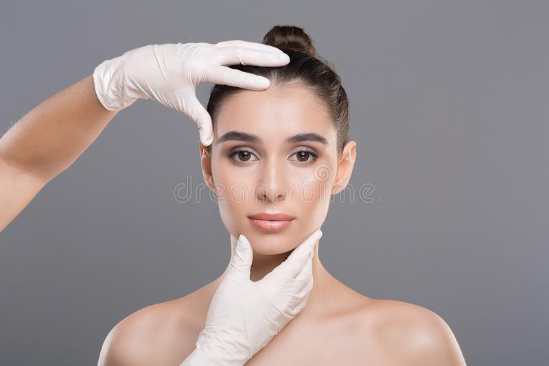 Doctor in gloves touch woman face, gray background. Female derma rejuvenate treatment. Doctor in gloves touch woman face, gray background stock image