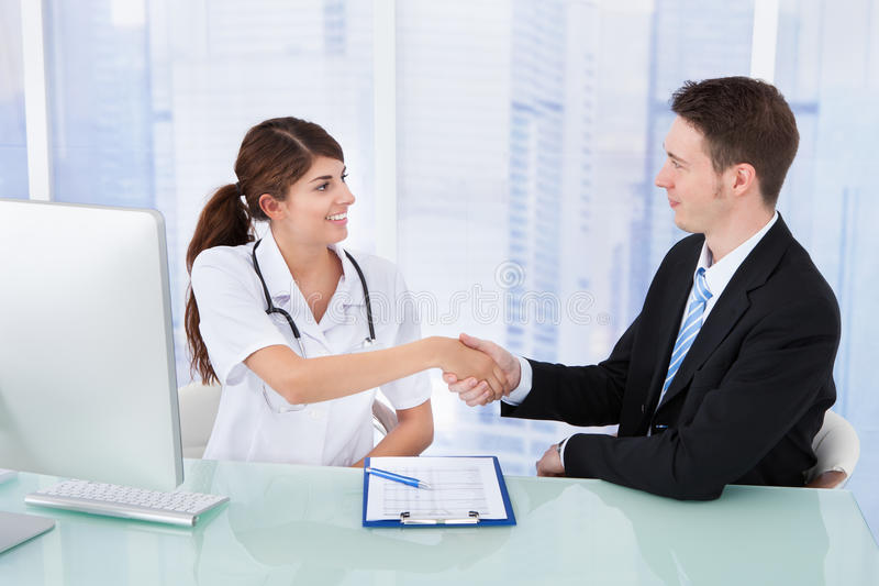 Doctor greeting businessman in clinic. Young female doctor greeting businessman at desk in clinic royalty free stock photo