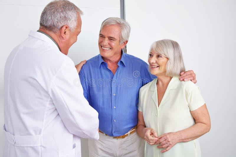 Doctor greeting senior couple with handshake royalty free stock photos