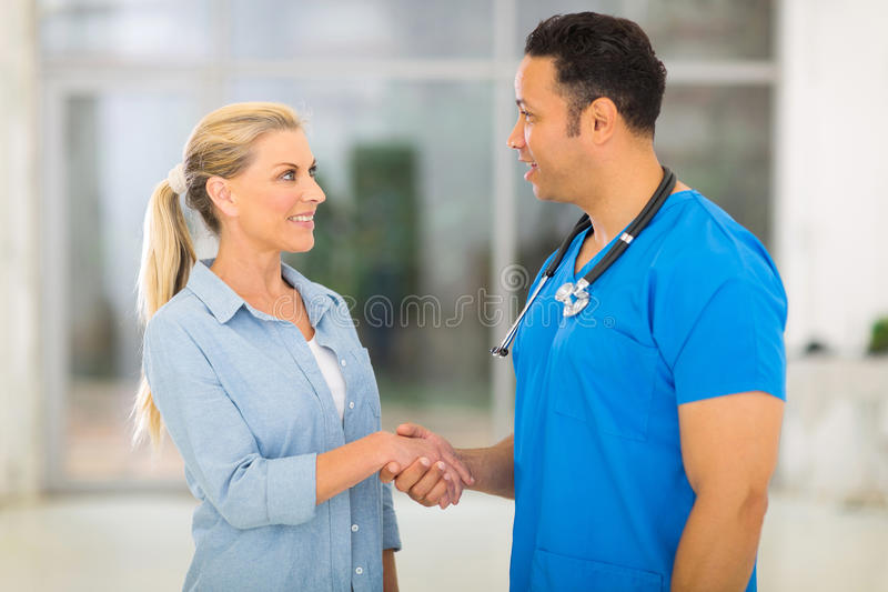 Doctor greeting senior patient. Caring medical doctor greeting senior patient stock images