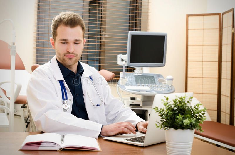 Doctor gynecologist working in office. Ultrasound in background stock photography