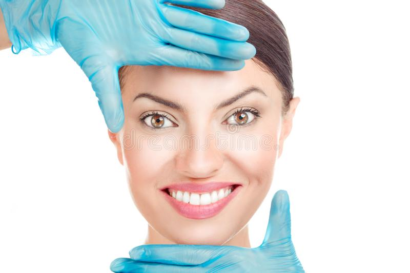 Doctor hand in gloves shaping a frame around face of a girl. Aesthetic procedure. Doctor hand in gloves shaping a frame around face of a girl. Woman with plastic stock photo