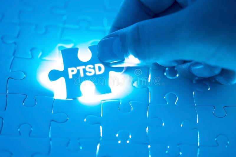 Doctor hand holding a jigsaw puzzle with PTSD - post traumatic s. Tress disorder. War veteran mental health issue word. Concept Healthy royalty free stock photography