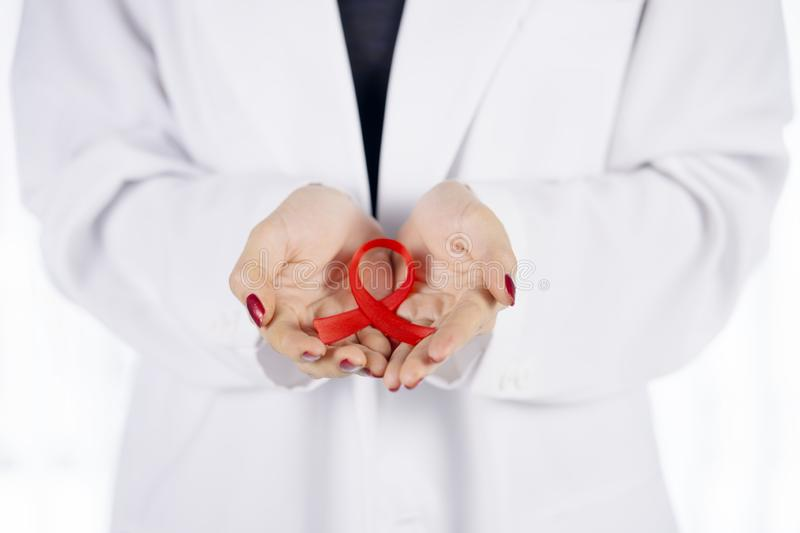 Doctor hand holding a world AIDS day ribbon royalty free stock photography