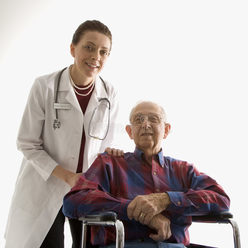 Doctor With Hands On Elderly Man S Shoulder In Wheelchair. Royalty Free Stock Photos