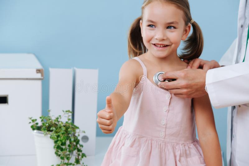 Doctor hands examining a cheerful child girl in a hospital. She shows thumbs up. royalty free stock photos