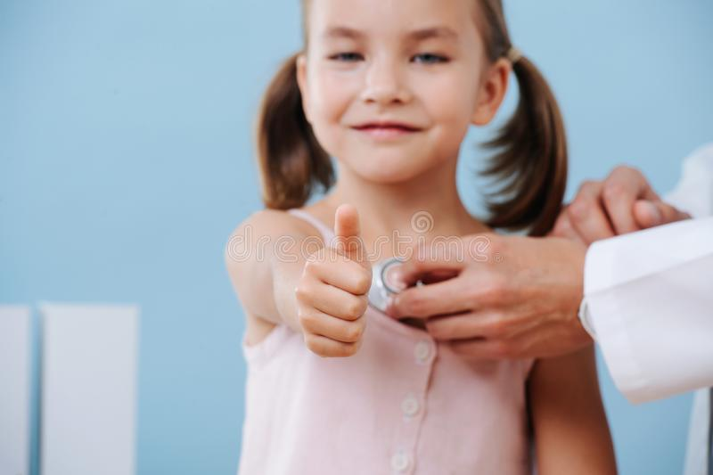 Doctor hands examining a cheerful child girl in a hospital. She shows thumbs up. royalty free stock image