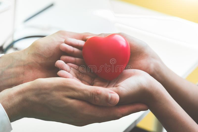 Doctor hands holding and giving red massage heart to patient little children for recover from sickness. Hospital and Healthcare stock images