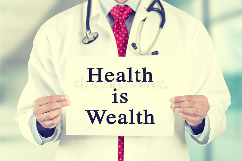 Doctor hands holding white card sign with health is wealth text message royalty free stock photography