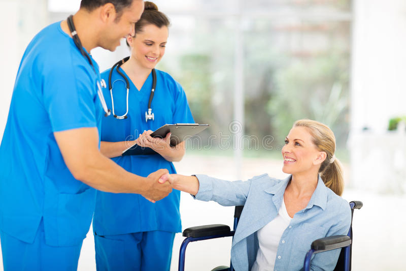 Doctor handshaking patient. Friendly middle aged medical doctor handshaking with patient on wheelchair royalty free stock images