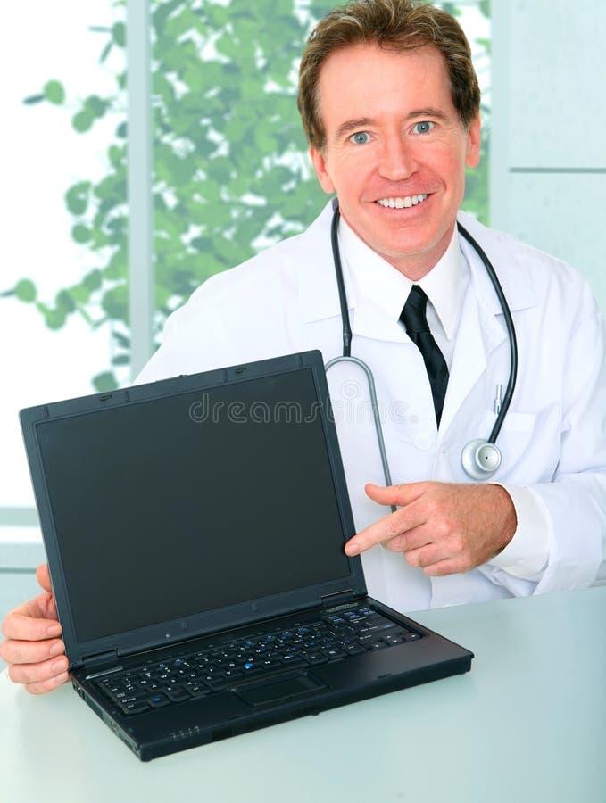 doctor hans bärbar datorkontor som presenterar pensionären arkivfoto