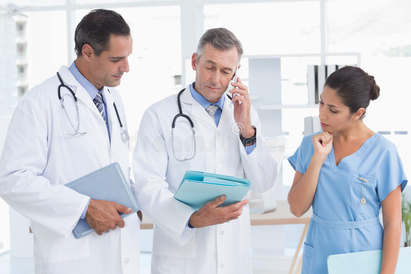 Doctor having phone call while his colleague speaking. In medical office royalty free stock image