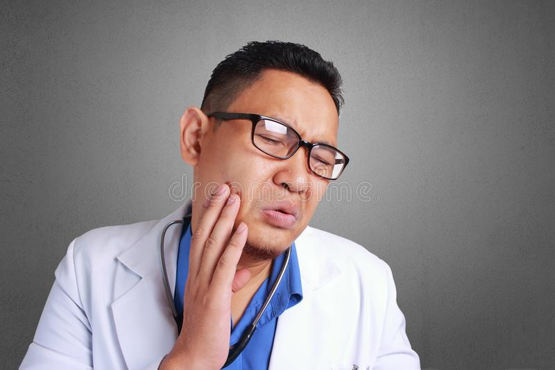 Doctor Having Tooth Ache. Young Asian Doctor with Eyeglass Having Tooth Ache stock image
