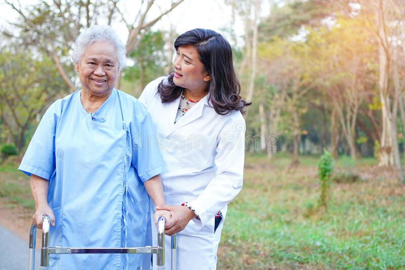 Doctor help and care Asian senior or elderly old lady woman use walker in park. stock photos