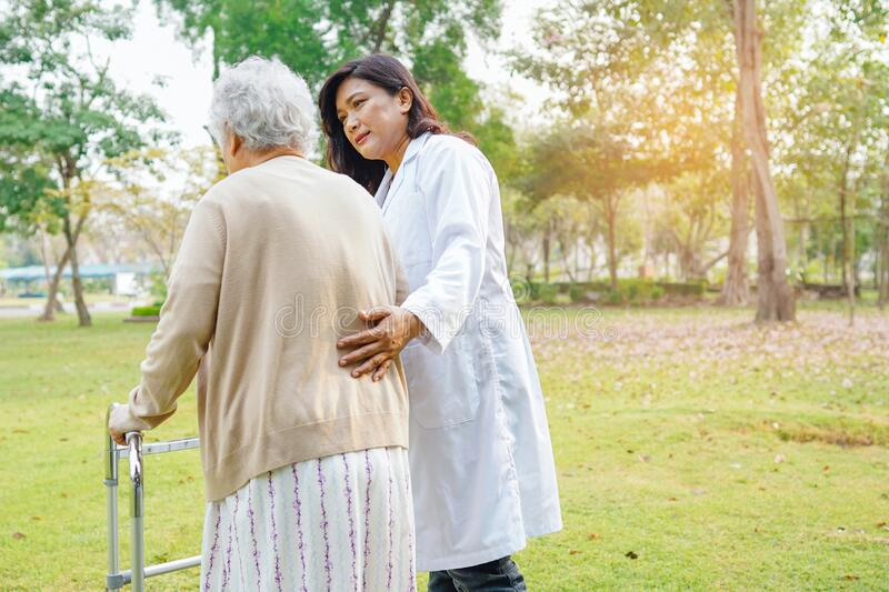 Doctor help and care Asian senior or elderly old lady woman use walker with strong health stock photography