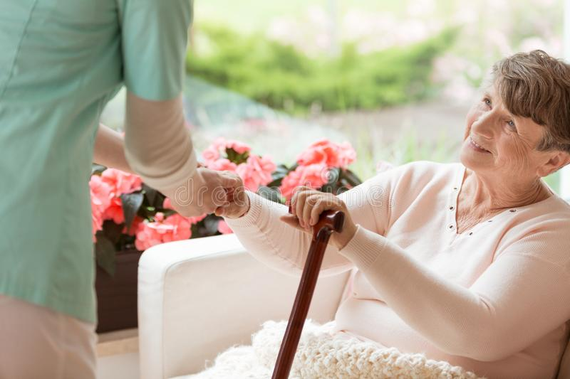 Doctor helping an elderly woman with Parkinson`s disease get up royalty free stock photography