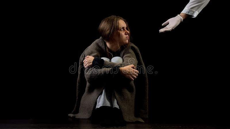 Doctor helping hand offering support to abused woman, therapy for addicted royalty free stock photo