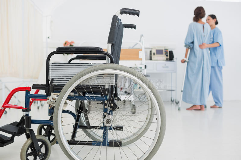 Doctor helping patient to walk with wheelchair in foreground royalty free stock photos