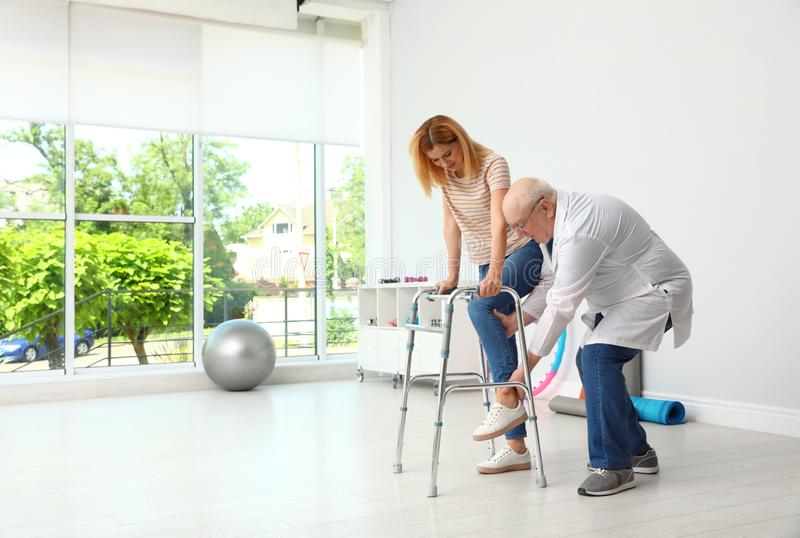 Doctor helping woman with walking frame stock photos