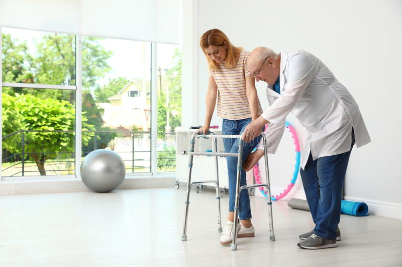 Doctor helping woman with walking frame royalty free stock image