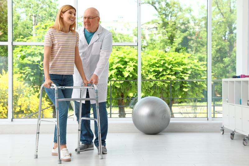 Doctor helping woman with walking frame stock images