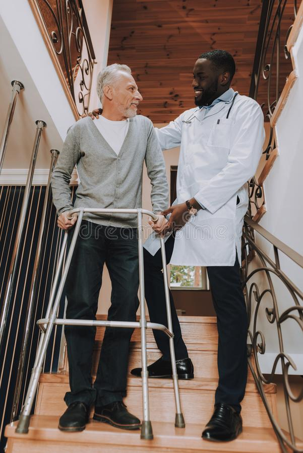 Doctor Helps. Pensioner on Go-Carts. Caregiver. Man Go Down. Stairs. Nursing Home. Man Holds On. Walker for Adults. Hard Walk Alone. Supports Man. Adult stock photo