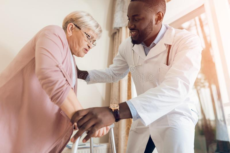 The doctor helps to get out of bed an elderly woman in a nursing home. royalty free stock photo