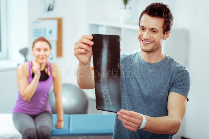 Doctor hermoso agradable que lleva a cabo una imagen del rayo X foto de archivo libre de regalías
