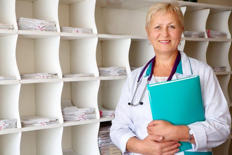 Doctor hermoso con la carpeta en gabinete imagenes de archivo