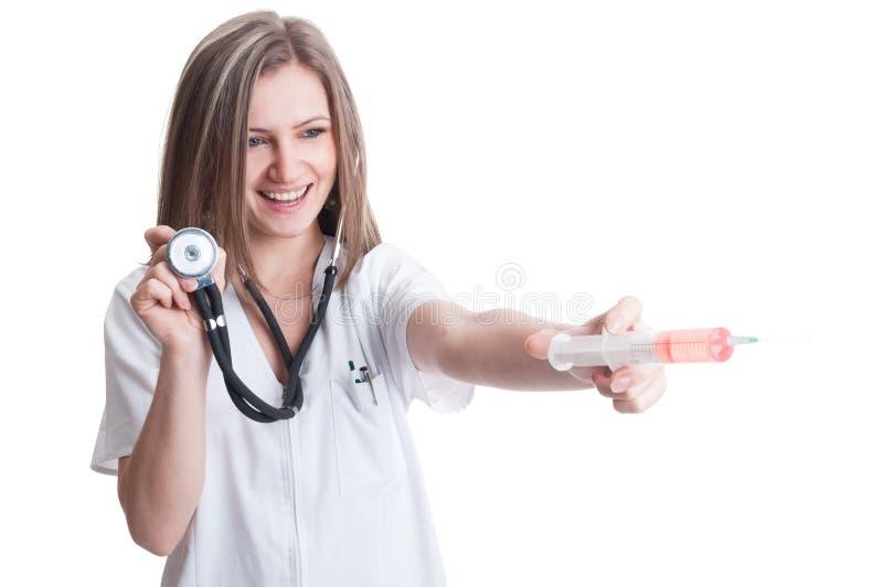 Doctor hermoso de la señora que sostiene el estetoscopio y la jeringuilla imagenes de archivo
