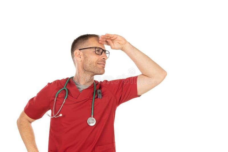 Doctor hermoso joven que mira lejos con gastos indirectos de la mano imagen de archivo libre de regalías