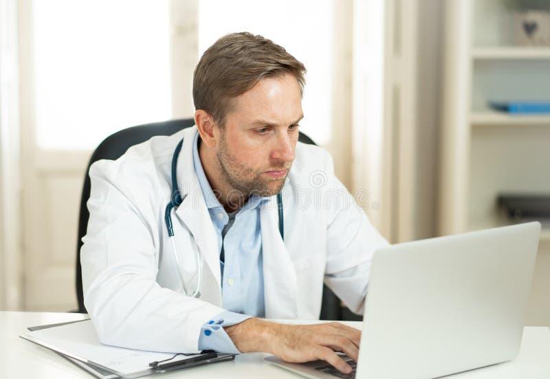 Doctor hermoso que trabaja en experiencia médica y que busca la información sobre el ordenador portátil en la oficina del hospita imagenes de archivo