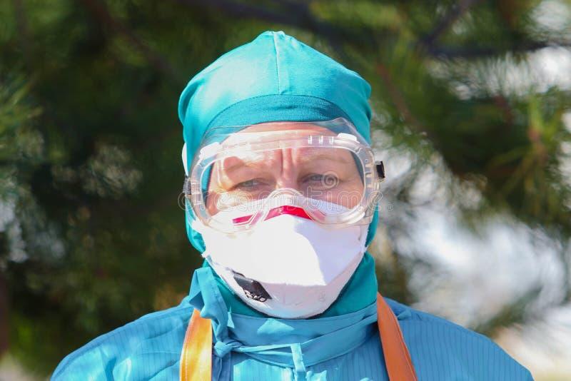 Doctor in het beschermende pak tijdens de aanval van het coronavirus COVID-19 in de namiddag stock afbeelding