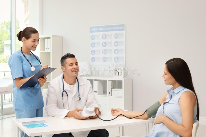 Doctor and his assistant checking pregnant woman`s. Blood pressure in hospital. Patient consultation stock photos