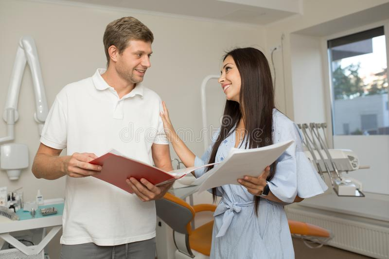 Doctor and his assistant looking in folder with paper. Dental office background.  stock photography