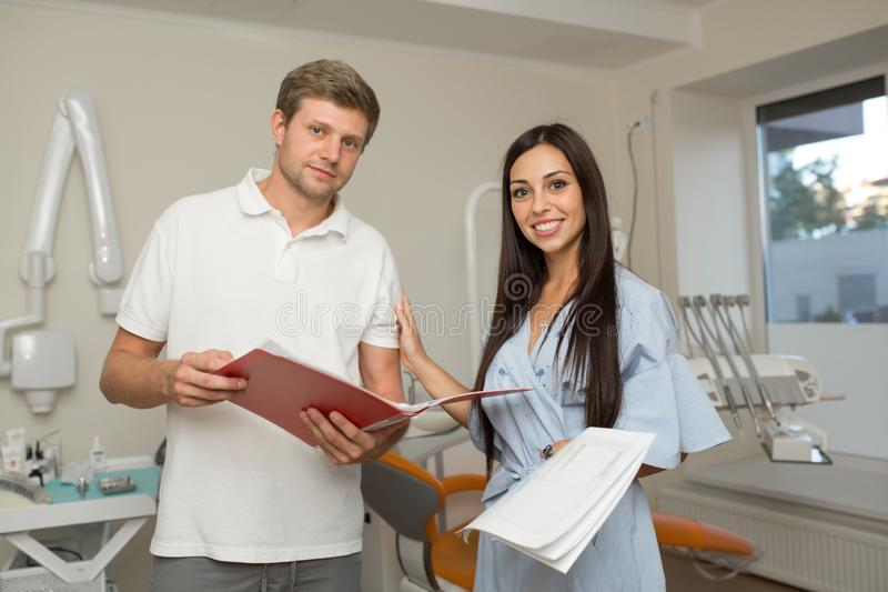 Doctor and his assistant looking in folder with paper. Dental office background.  royalty free stock photos