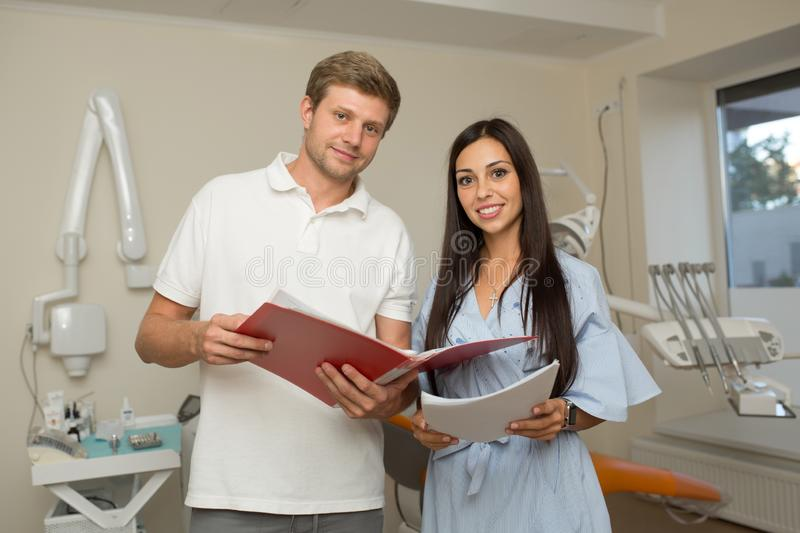 Doctor and his assistant looking in folder with paper. Dental office background.  royalty free stock images