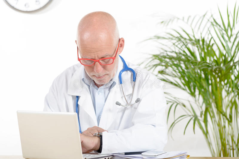 A doctor in his office with phone. A doctor phone in his office with red glasses stock images