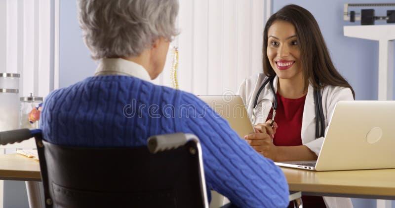 Doctor hispánico de la mujer que habla con el paciente mayor fotos de archivo