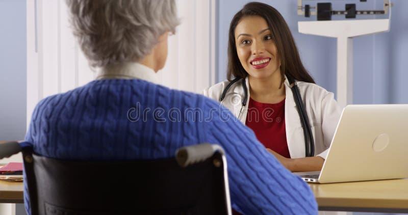 Doctor hispánico que comparte buenas noticias con el paciente fotografía de archivo