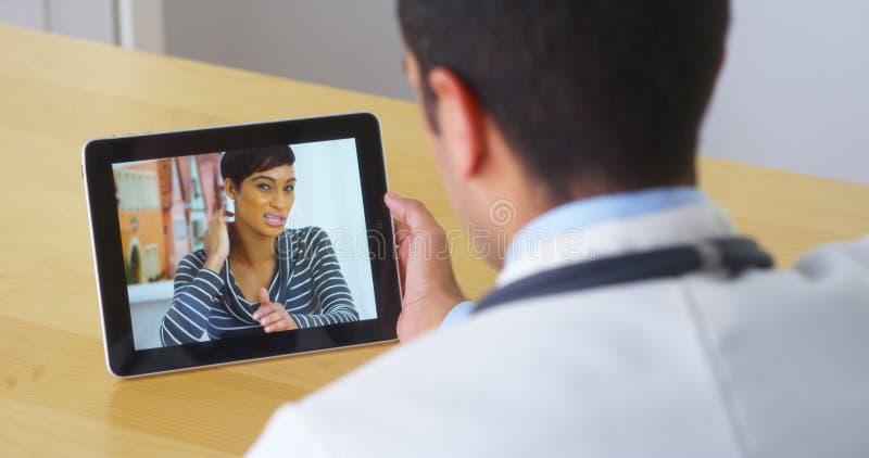 Doctor hispánico que habla con el paciente de la mujer joven en la tableta foto de archivo libre de regalías