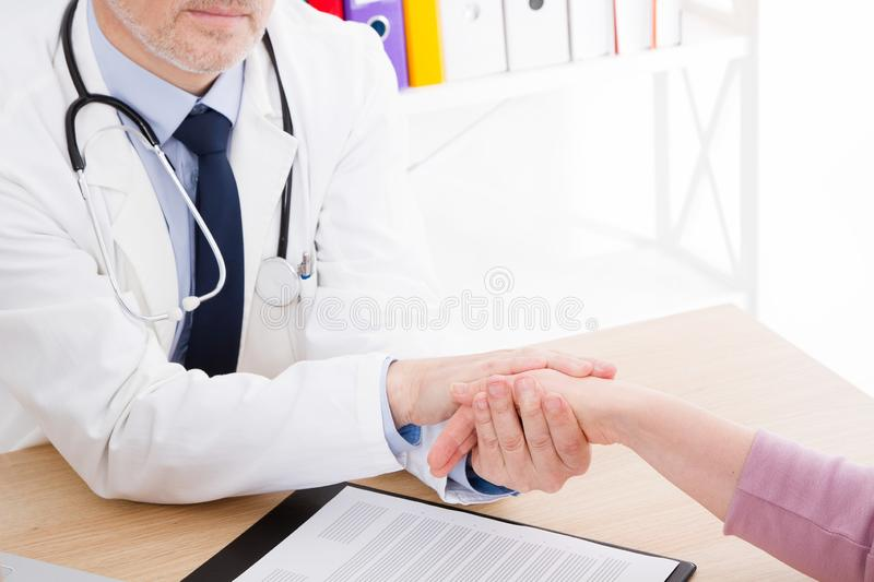 Doctor hold patient hand in office. Examination result, positive test, calm down, promise and cheer up. Medical insurance stock photos