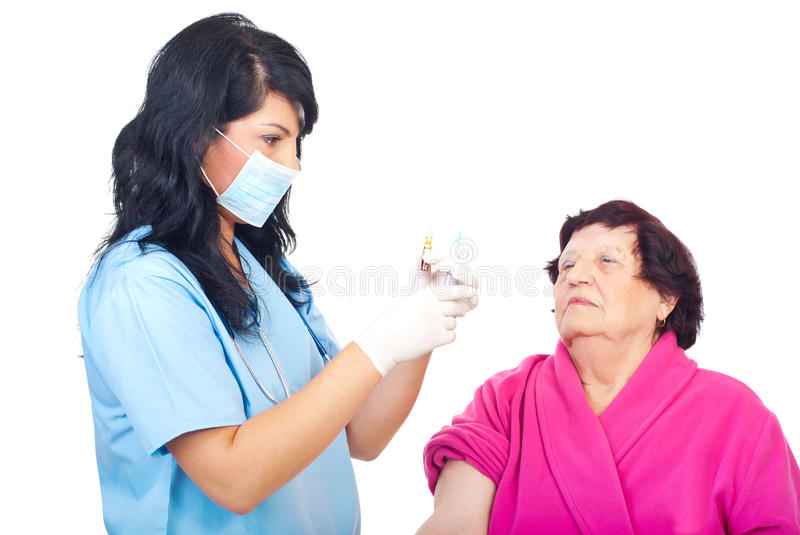 Doctor hold syringe and ampule with flu vaccine. Doctor woman holding a medical ampule with flu vaccine and a syringe and preparing to inject elderly patient stock image