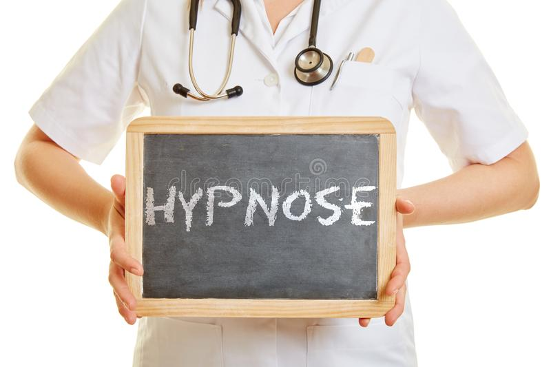 Doctor holding a blackboard with the german word Hypnose. As a concept against Burnout and stress royalty free stock photo